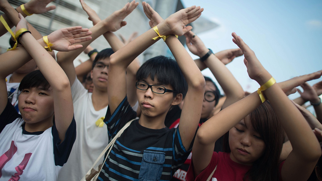 Student pro-democracy group Scholarism convenor Joshua Wong (C) makes a gesture at the Flag Raising Ceremony at Golden Bauhinia Square in Hong Kong