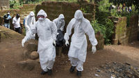 A burial team with the body of an Ebola victim in Freetown, Sierra Leone (Reuters)