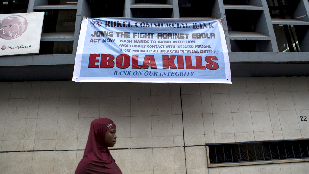 Woman passes an Ebola awareness sign in Freetown, Sierra Leone (Reuters)