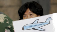 Bereaved relative holds up a drawing of the missing plane (Reuters)