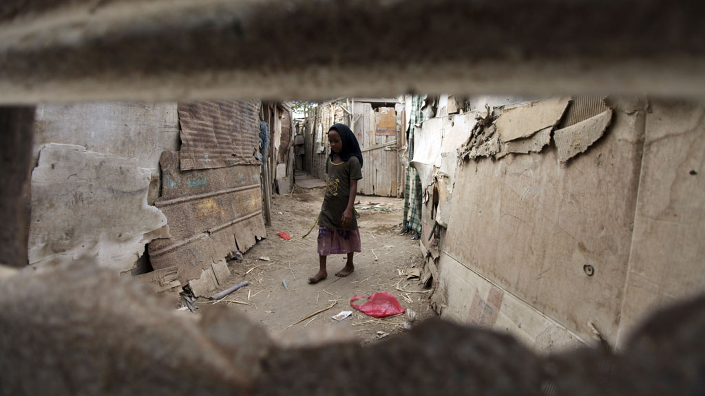 A girl outside her home, made of cardboard and wood, in the slums of Aden, southern Yemen