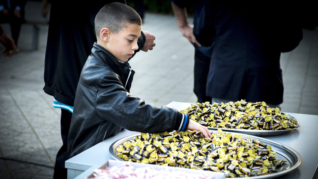 A boy takes a sweet at an Eid celebration in Rotterdam (Getty)