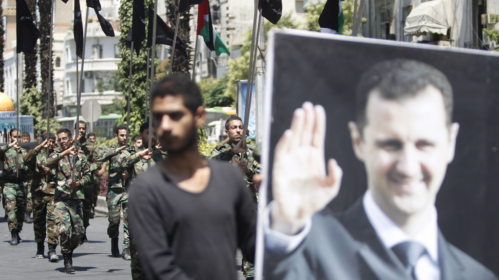 Syrian army soldier holds picture of Assad (Reuters)