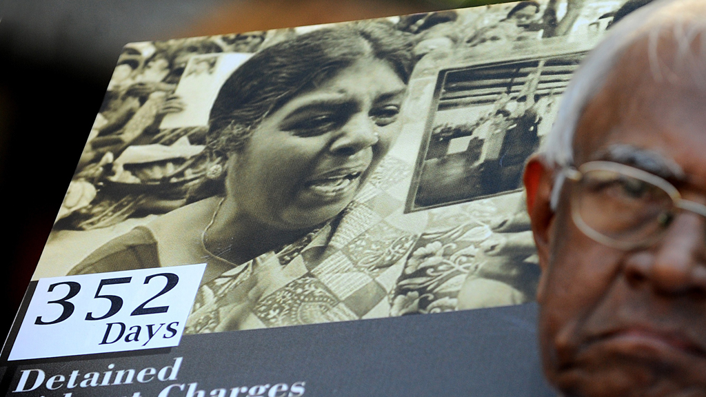 A protester holds a placard showing Jeyakumary Balendaran prior to her release.