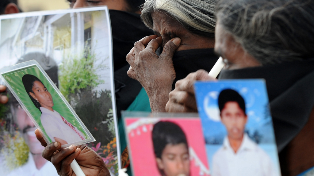 Tamil women in Jaffna hold up pictures of the dead and missing in November 2013.