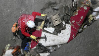 A member of the recovery team searches through crash debris on the mountainside (Reuters)