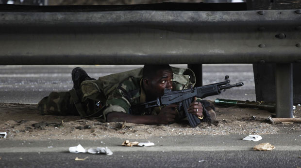 A soldier loyal to Alassane Ouattara takes cover in Abidjan (reuters)