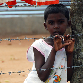 A young Tamil boy stands behind a barbed-wire fence in the Menikfam Vanni refugee camp located near the town of Chettekulam in northern Sri Lanka (Reuters)