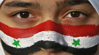 Protester with face painted in Syria flag colors shouts slogans outside Syrian embassy in Amman (Reuters)