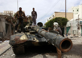 Rebel fighters stand on top of a captured tank belonging to forces loyal to Muammar Gaddafi