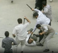 Basij members in civilian clothes attack with batons.