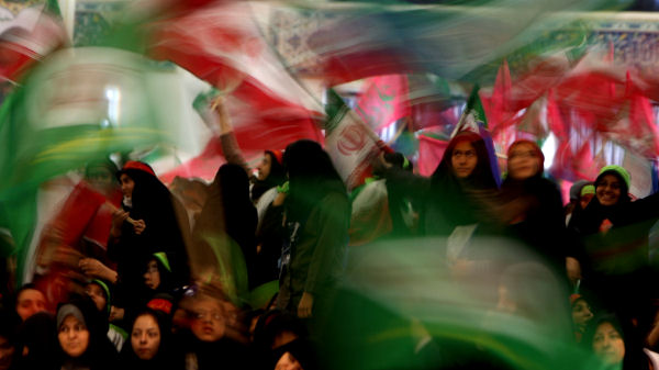 Members of Iran's Basij Islamist militia wave Iranian flags. (Getty)