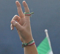 An Iranian woman flashes the V-sign of victory, with the colours of the national flag around her finger and wrist. (Getty)