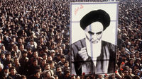 January 1979: Iranian protestors hold a up a poster of Ayatollah Khomeini. (Getty)