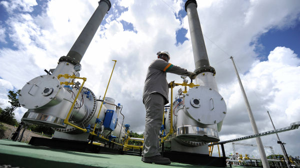 A technician of the Brazilian state oil company Petrobras works on a machine at a natural gas pipeline. (Getty)