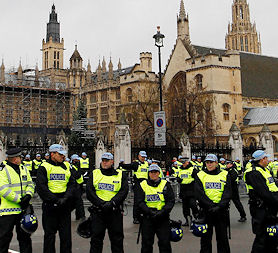 Police officers form a line in front of the Houses of Parliament as student protesters gather nearby (Reuters)