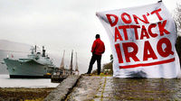 Anti-war protestors stand on the shores of Loch Long in Scotland where HMS Ark Royal has been berthed since Monday to take on board supplies, before heading to the Gulf, January 14, 2003 (Credit: Reut