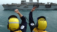 Crewman on the HMS Ark Royal playfully gesture to the crew of the HMS Ocean as they sail to the Gulf