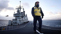 Chief Petty Officer Downs walks on the deck of the British carrier HMS Ark Royal
