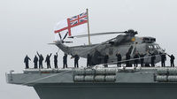 Sailors wave to crowds on the shore, from the stern of the aircraft carrier HMS Ark Royal as she enters harbour