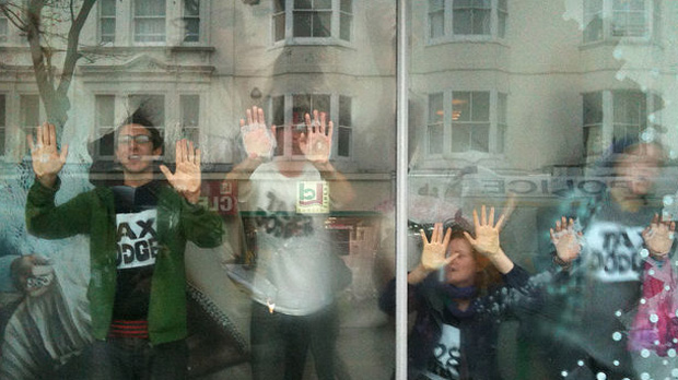 Topshop protests: demonstrators glue their hands to the window in Brighton. (Credit: Cathy Jones)