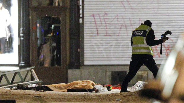 Police forensics expert examines the remains of a suspected suicide bomber in central Stockholm (Reuters)