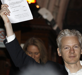 WikiLeaks editor Julian Assange emerges from the High Court. (Reuters)