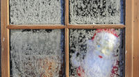 A toy Santa Claus is seen through the frosted window of a garden shed near Boroughbridge (Reuters)