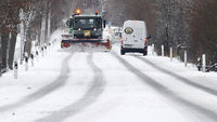 Cars make their way slowly as snowploughs clear a road. London's Gatwick airport has shut its runway while British Airways cancels all flights from Heathrow, on a day of snow chaos. Reuters