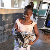 Rose Soko holds her new-born grandson as her daughter Patricia lies in the van upon her arrival at a hospital in Gbarnga on December 4, 2008. Patricia, 21, almost died in childbirth. (Getty)
