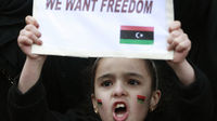 Libya: young girl holds up anti-Gaddafi placard. (Reuters)