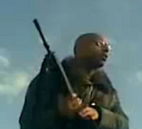 Saif Gaddafi rallies supporters in Libya, with gun.