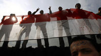 Protesters hold up the Egyptian flag. (Reuters)
