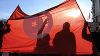 People are seen through a Tunisian national flag as groups of Tunisians and supporters demonstrate in Lyon, eastern France, on January 15, 2011 (Getty)