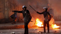 Riot police walk past burning tyres placed to form a barricade during clashes in Cairo (Reuters)