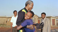 Anti-apartheid leader and African National Congress (ANC) member Nelson Mandela hugs, October 1990, a young Sowetan girl as he visits the black township near Johannesburg. (Getty)