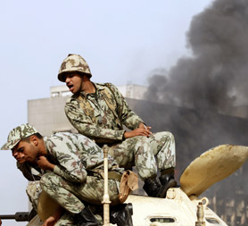 Egypt protests: soldiers in Cairo look down from a tank. (Reuters)
