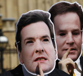 David Cameron, Eric Pickles, George Osborne and Nick Clegg depicted by masks. (Reuters)