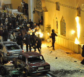 Egyptian riot police attempt to put out fire started by Christians outside a mosque in Alexandria following a church bombing which killed 21. (Reuters)