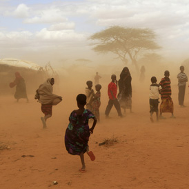 Newly-arrived refugees run away from a cloud of dust at the Dagahaley refugee camp in Dadaab (Reuters)