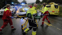 Rescue personnel push an injured victim away from the camp site in Utoya (Reuters)