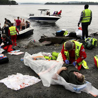 A wounded woman is brought ashore opposite Utoya island in Norway after being rescued from a gunman who went on a killing rampage (Getty)