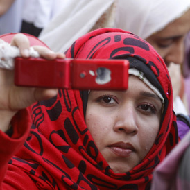 Woman using her phone to document a protest at Cairo University (Getty)