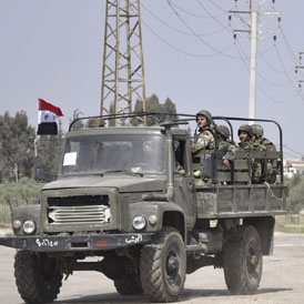 Syrian army vehicles leave the southern town of Deraa (Reuters)