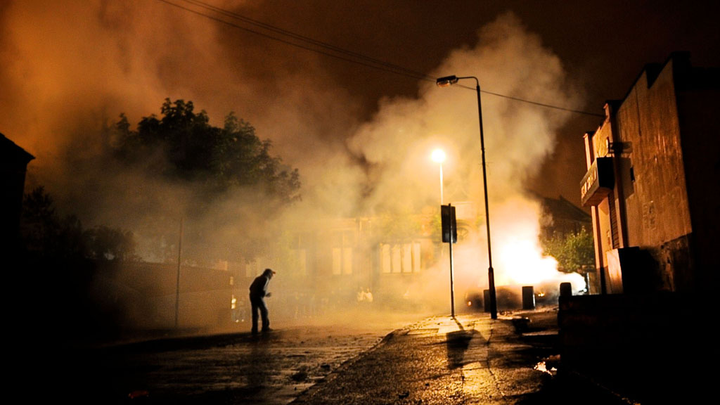 A protester is sihouetted in the flames of East Belfast (Getty).