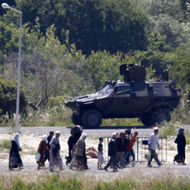 Syrian refugees walk past Turkish forces in Hatay (Reuters)