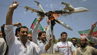 Activists hold up a burning mock drone aircraft during a rally in Peshawar. (Reuters)