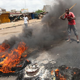 Anti-Gbagbo protesters near a roadblock and burning tyres in the Abobo area of Abidjan (reuters)