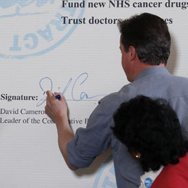 David Cameron signs his NHS pledge during the General Election campaign (R)