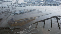 Sendai Airport in Japan is flooded by tsunami waters (Reuters)